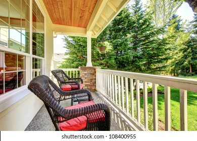 Front covered porch with brown chairs and red cushions.