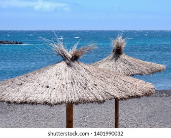 in front of the dark blue atlantic ocean, two reet grass parasols stand by the water on a dark volcanic beach in close-up.over it dark blue sky, picture without people