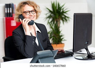 Front desk lady attending call and working on computer