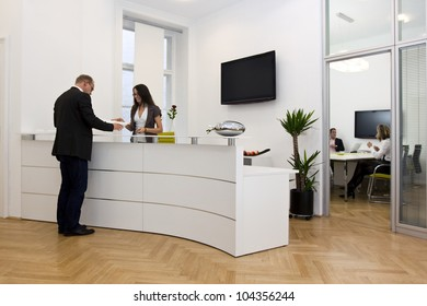 A front desk lady doing her job very well and cheerfully while she's consulting a customer. The black space on the TV-screen could be used for any logos, some label signs or any graphic additions.