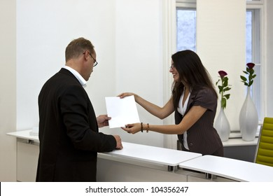 A front desk lady doing her job very well and cheerfully while she's consulting a customer.  The white space on the sheet of paper could be used for any graphic additions.