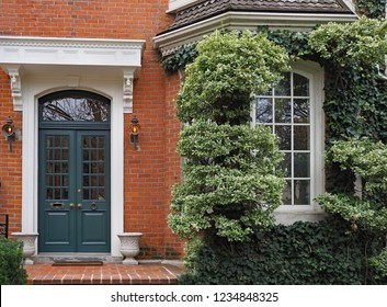 front door of brick townhouse with window surrounded by vines