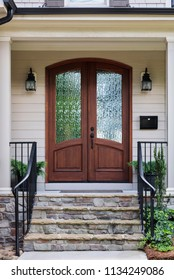 Front door, brown front dual doors with a nice stone staircase with black hand railing