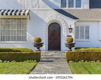 Vordertür des klassischen Hauses mit grünem Hedgepfad.