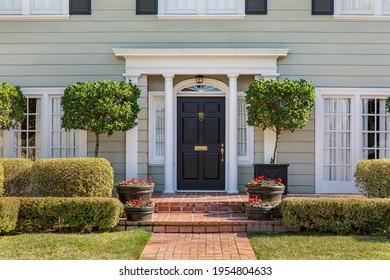 Vortür des klassischen Hauses mit angelegten Vorgarten- und Ziegelpfaden.