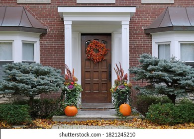 Front door with colorful fall wreath and pumpkins