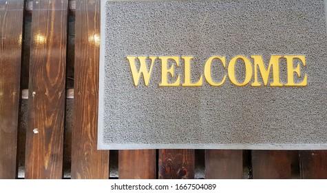 Front door with doormat plants with welcome written on it