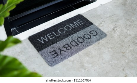 Front door with doormat plants with welcome,goodbye written on it