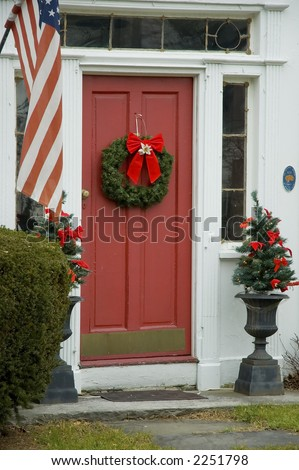 The Front Door Of An Early New England House With A Wreath Hanging On A Red