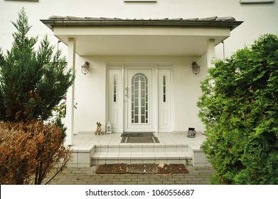 Front door entrance from luxury house. Principal entrance of an luxury house with small dog statue at entrance.