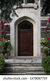 front door of gothic style stone house with floral planters and flagstone steps