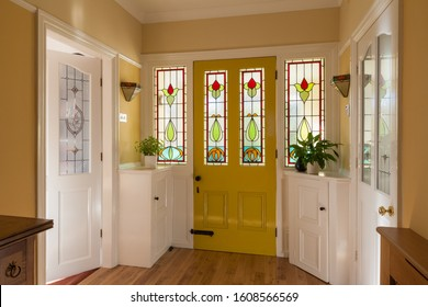 Front door and hallway of a house in England with stained glass window in the door.