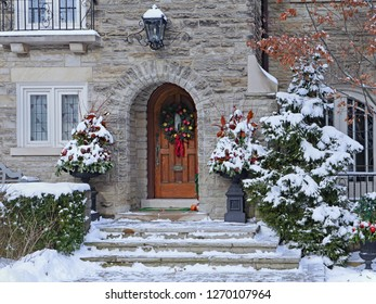 front door of house with snow and Christmas ornaments