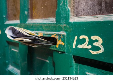 Front door letter slot full of newspapers