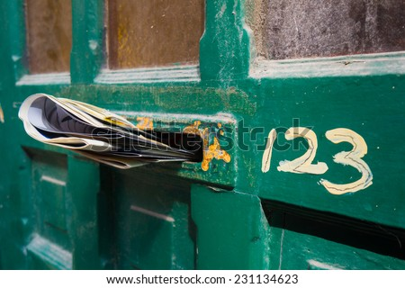 Front door letter slot full of newspapers