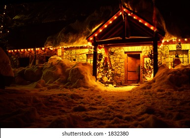 front door of night lit stone lodge in winter snow at Christmas