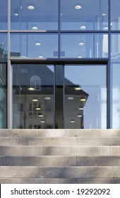 The front door of a office block, reflecting  buildings in the glass