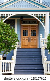 Front door of an old blue Victorian cottage in the San Francisco area