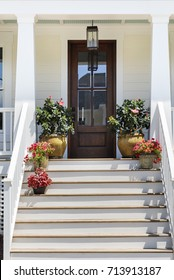 Front door with potted flowers flanking the sides