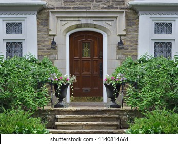 front door of stone faced house with shrubs