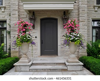 front door of stone house with large flower pots