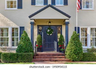 Haustür im traditionellen Stil mit gepflastertem Ziegelweg.