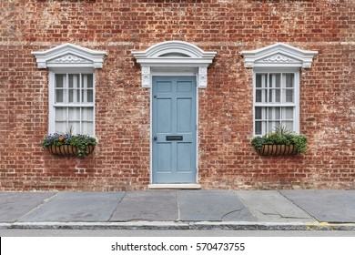 Front door and two windows with portico creating a beautiful design
