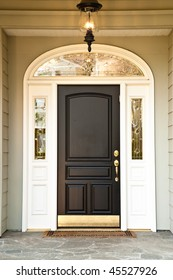 Front door of an upscale home with an illuminated porch light. Vertical format.