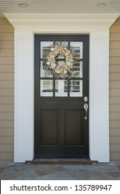 Front door of an upscale home/Vertical shot of a black front door on an upscale home with a wreath and windows with reflection.