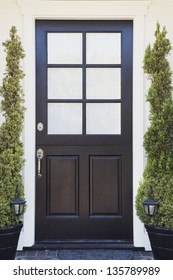 Front door of an upscale home/vertical shot of a black front door of an upscale home with white windows, plants, porch lights and stone flooring