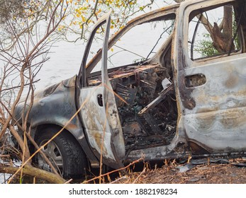 Front driver side of wrecked and burned out car on riverbank in New Orleans, Louisiana, USA