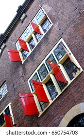 the front of a dutch house in Amsterdam with open red shutters