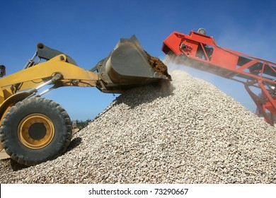 Front end loader and conveyor belt on a pile of graded stone