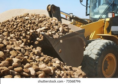front end loader machine scooping up big stones in a quarry
