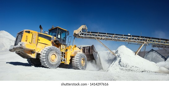 Front end loader near the stone crushing equipment at the limestone quarry against the blue sky, panoramic image. Mining industry.