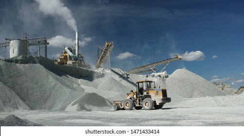 Front end loader near the stone crushing equipment at the limestone quarry, panorama. Quarry mining machinery.
