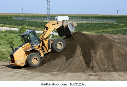 front end loader putting dirt on top of a mound