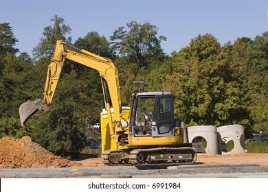 A front end loader shoveling dirt into a dump truck