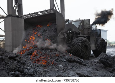 front end loaders with traction chains on wheels removing hot slag from electric arc furnace