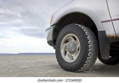 Front end and rugged tire of a truck on a vast desert playa