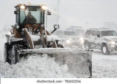 Front End Wheel Loader removes (clearing ) snow from road during snow winter storm, poor visibility. Winter highway maintenance in Petropavlovsk-Kamchatsky City. Kamchatka Peninsula, Russian Far East.