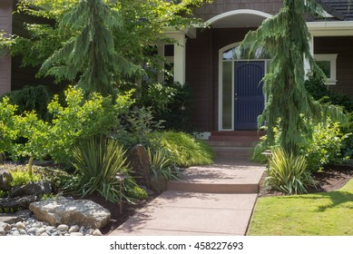Front entrance to a contemporary home in the Pacific Northwest is almost hidden by beautiful landscaping.