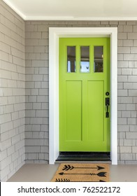 A front entrance of a home with a green entry door, front door