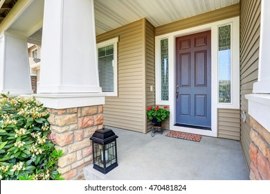 Front entry door with concrete floor porch and flowers pot. Northwest, USA