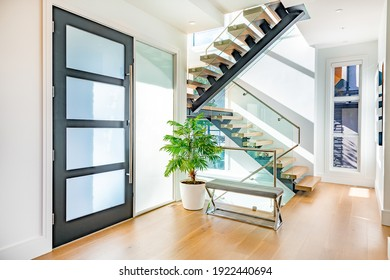 Front entry door with contemporary glass staircase