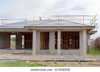 Front exterior of a block brick home being built in suburbia