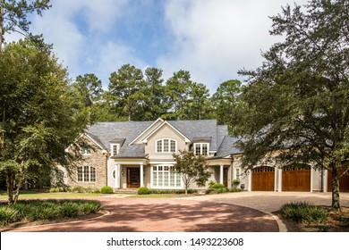Front exterior view of large upscale house home with triple garage and columns on a secluded large lot with curb appeal