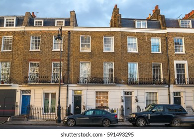 Front facade of flat buildings in london with two cars  parked at the door