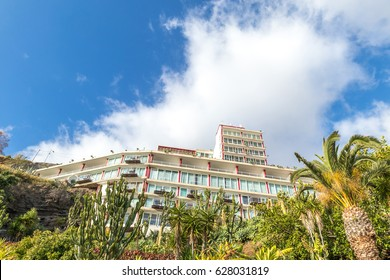 The front facade of a  hotel in Madeira Island with many cactus seen from below with a blue sky and a white cloud on top
