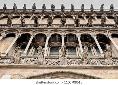 The front facade of the Notre Dame cathedral in Dijon, France, is lined with different gargoyles looking out over the city.
